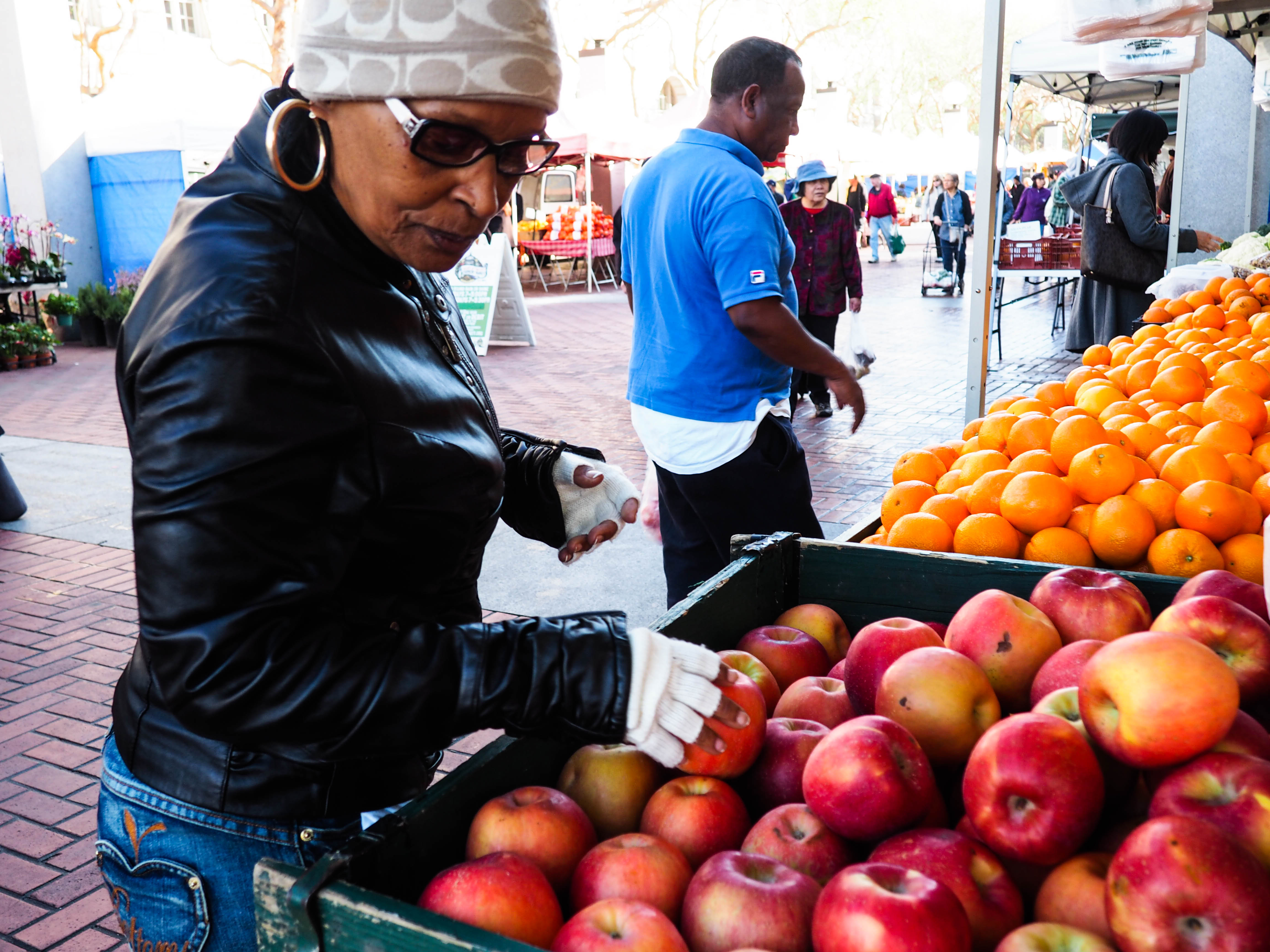 Woman Searching Through Apples on Display at Farmer's Market