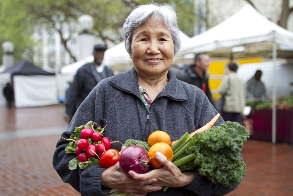 Older Asian Woman Holding Vegetables