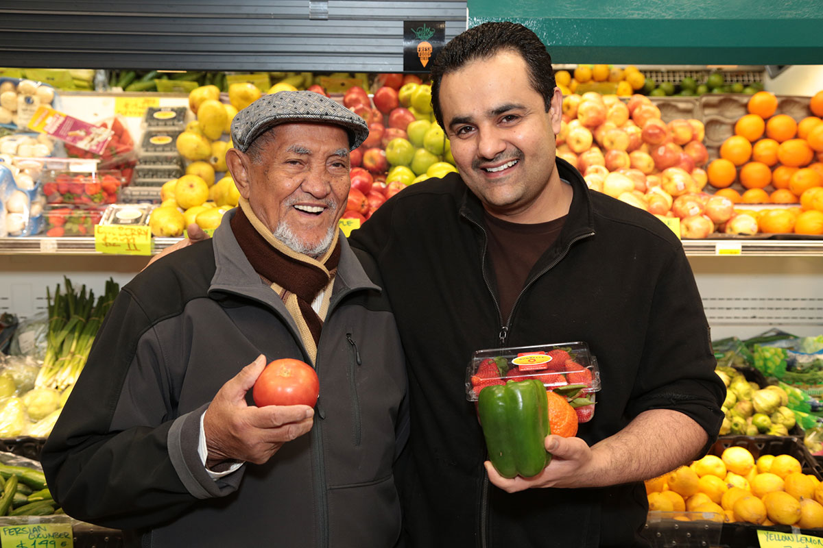 Men Holding Fruit at Grocery Store