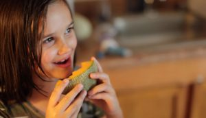 Child Eating Cantaloupe